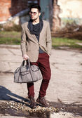 Sexy fashion man model dressed elegant holding a bag posing outd — Foto Stock