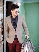 Sexy fashion man model dressed elegant holding a bag posing outdoor — Stok fotoğraf