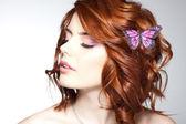 Hübsche frau mit einem schmetterling im haar - beautyshot — Stockfoto
