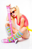 Sexy baseball girl wearing colorfull clothes posing with a baseball bat — Stock Photo