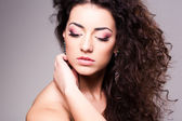 Cute girl with curly hair wearing make-up - studio shot — Stock Photo