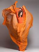 красивая женщина в длинные оранжевое платье позирует динамических в студии — Стоковое фото