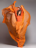 Beautiful woman in long orange dress posing dynamic in the studio — 图库照片