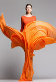 Beautiful woman in long orange dress posing dynamic in the studio — Zdjęcie stockowe