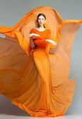 Piękna kobieta w długo pomarańczowa sukienka pozowanie dynamiczne w studio — Zdjęcie stockowe