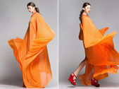 Beautiful woman in long orange dress posing dynamic in the studio — Stock Photo