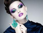 Profissional maquiagem azul e penteado no rosto de mulher bonita — Foto Stock