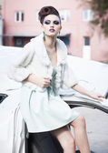 Beautiful woman model in white dress, fur and high-heels wearing blue make-up posing outdoor — 图库照片