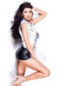 Sexy woman wearing leather shorts and denim jacket on white background — Stock Photo