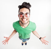 Funny handsome man with hipster glasses showing his palms and smiling large - wide angle shot — Foto de Stock