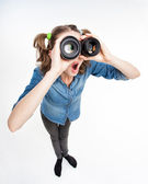 Cute funny girl with two pony tails looking thru photo lenses- wide angle shot — Foto Stock