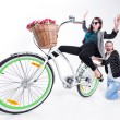 Two girls riding a bike making funny faces - isolated on bluish background — Stock Photo