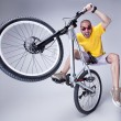 Crazy boy on dirt jump bike on grey background - wide studio s — Stock Photo #28865703