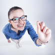 Pretty girl with perfect teeth wearing geek glasses smiling and playing with chuwing gum — Stock Photo #28865927