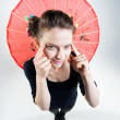 Cute girl holding a chinese umbrella and stretching eyes — Stock Photo