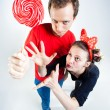 Stock Photo: Funny couple playing with lollipop in studio