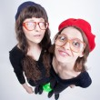 Two cute girls wearing granny's glasses having fun and making funny faces — Stock Photo