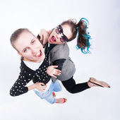 Two girls making funny faces - isolated on bluish background — Stock Photo