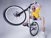 Crazy boy on a dirt jump bike on grey background - wide studio s — Stock Photo