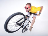 Crazy boy on a dirt jump bike making funny faces- wide studio sh — Stock Photo