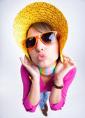 Pretty girl with yellow summer hat giving a kiss — Stock Photo