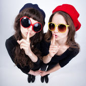 Two cute girls showing quiet with their fingers cross their lips — Stock Photo