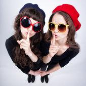 Dudakları ile parmaklarını sessiz gösterilen iki sevimli kız çapraz — Stok fotoğraf