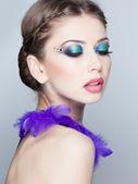 Beautiful model wearing blue make-up - studio shot on grey — Stock Photo