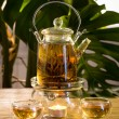 Chinese teapot with tea, on a burning support from glass - Stock Photo