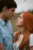Happy young couple kissing on a ripe field — Stock Photo