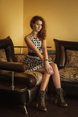 Beautiful young woman sitting in a shoes — Stock Photo