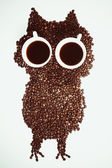 Conceptual owl made with coffee beans and cups — Stock Photo