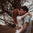 Stock Photo: Outdoor portrait of young couple kissing in summer field