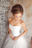 Beautiful Bride lit by sunlight from a window. beautiful young bride standing beside a large window — Stock Photo