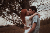 Outdoor portrait of young couple kissing in summer field — Stock Photo