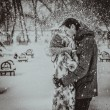 Young couple kissing on snow. Black and white. — Stock Photo #43163903