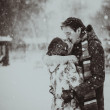 Young couple kissing on snow. Black and white. — Stock Photo #43163983
