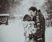 Young couple kissing on snow. Black and white. — Stock Photo