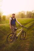 Jeune homme beau, posant sur le pré vert avec moto vintage — Photo