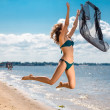 Jumping happy girl on the beach, fit sporty healthy sexy body in bikini — Stock Photo #50845023