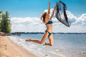 Jumping happy girl on the beach, fit sporty healthy sexy body in bikini — Stock Photo