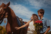 Young beautiful couple  with a horse. Filtered. Selective focus. — Stock Photo