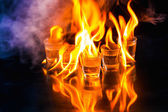 Glasses with burning alcohol on black background — Stock Photo