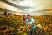 Láska pár stojící venku ve slunečnicovém poli — Stock fotografie