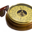 Barometer - aneroid on a white background and black sunglasses — Stock Photo