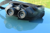 Binoculars in the pouch on the hood of the car. — Stockfoto