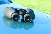 Jumelles se trouvant sur le capot de la voiture. — Photo