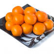 Large ripe tangerines in a glass dish on a white background. — Stock Photo