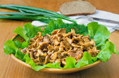 Fried mushrooms of chanterelle on a dish together with lettuce l — Photo