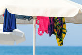Sunshades and clothes on a sea beach   — Stock Photo